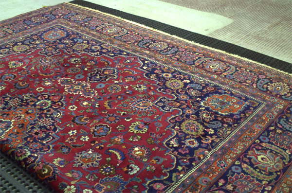 Rugs laid out for dust removal during the Oriental rug cleaning process